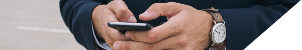 Banner image of a man typing on a cell phone.